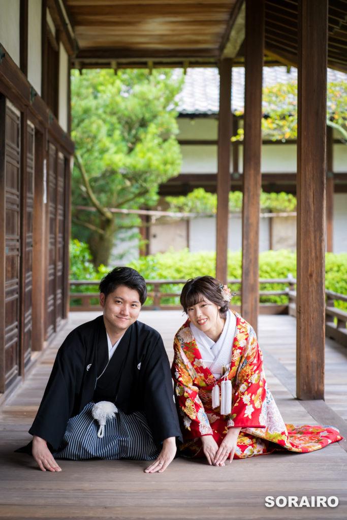 お寺の廊下に正座する和装姿の男女