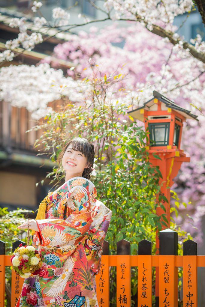 桜をバックに笑顔で上を見上げる和装姿の新婦