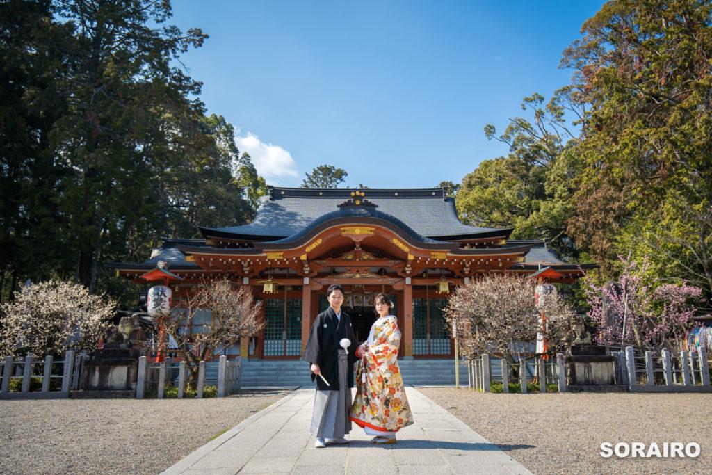 長岡天満宮の本殿の前で和装姿でカメラ目線で立っている新郎新婦