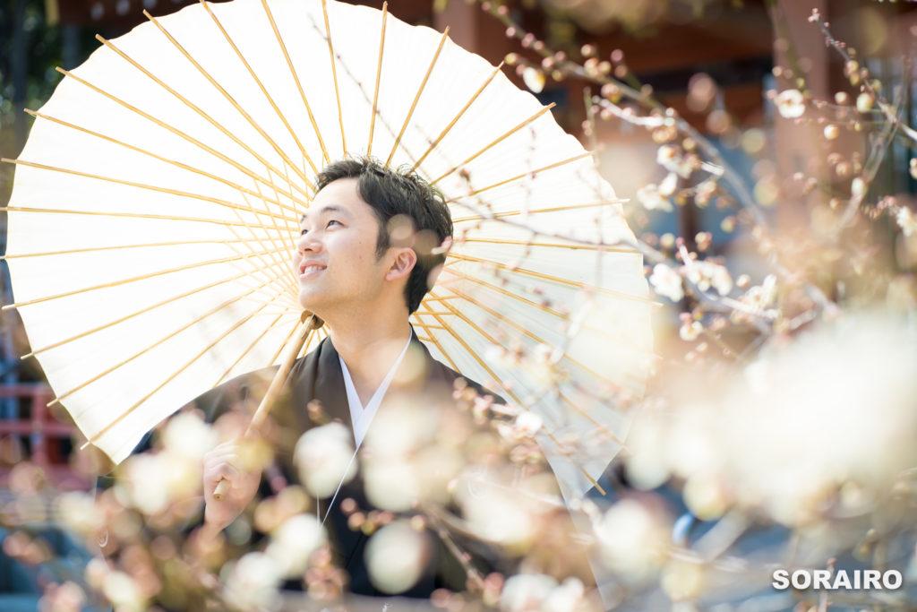 梅の花の間から見える和装姿の新郎