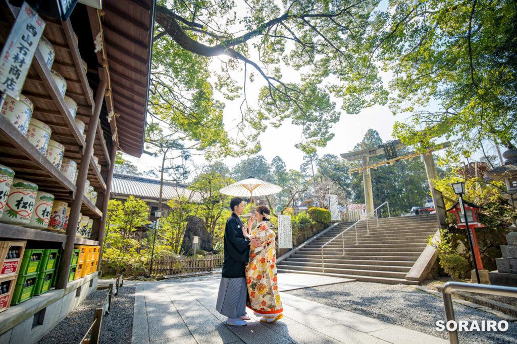 長岡天満宮の境内で和傘の下で見つめ合う和装姿の新郎新婦