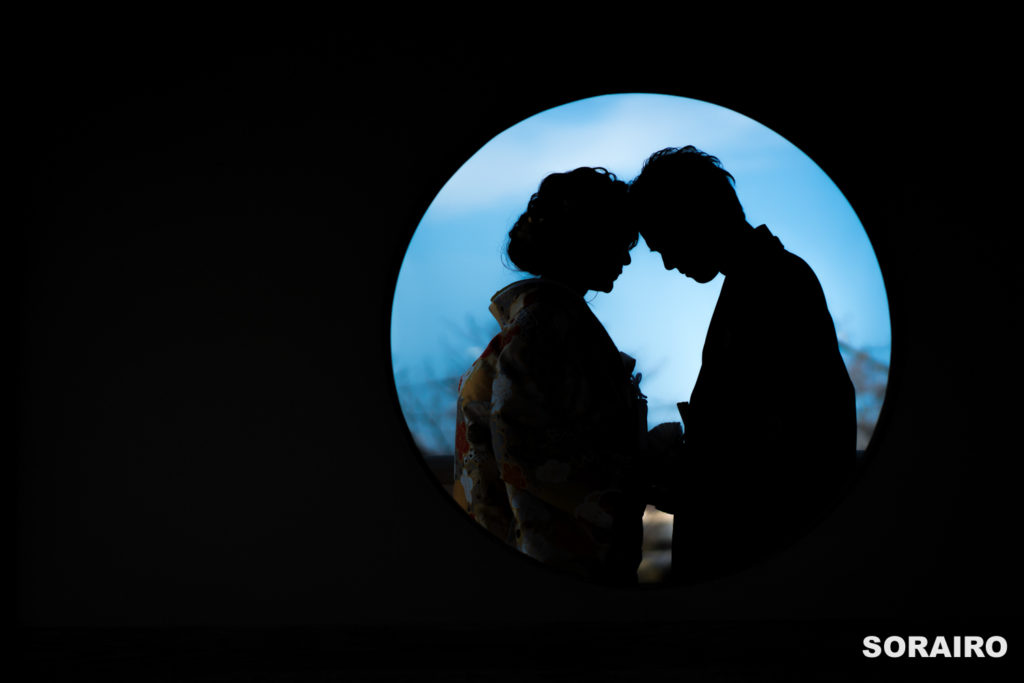 丸窓から覗く男女のシルエット