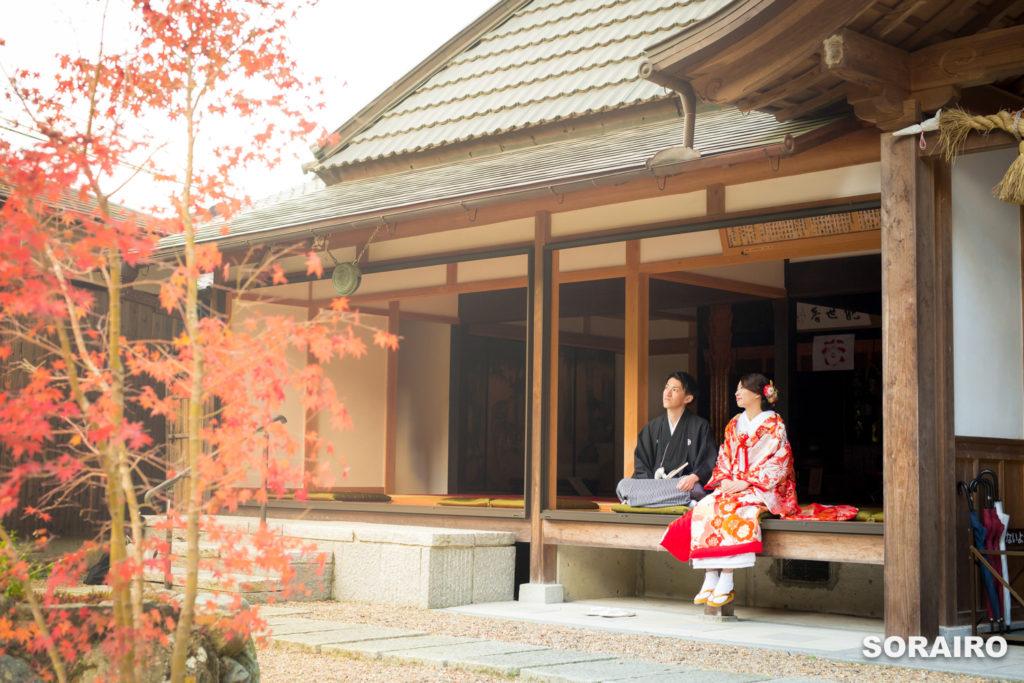 正寿院の縁側に腰掛け外を見つめる和装姿の新郎新婦